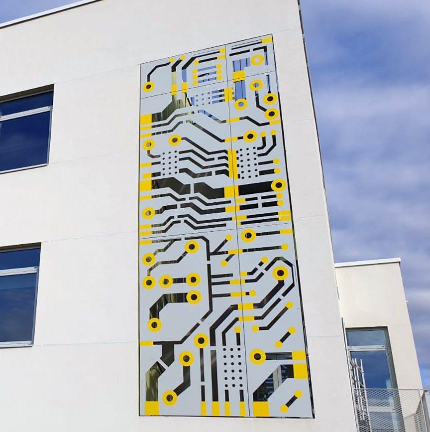 Design en métal sous forme de connexion réseau incrusté dans la façade du bâtiment P24