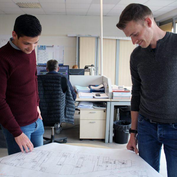 Deux employés du bureau d'études regardent un plan du chantier